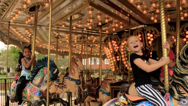 Students from a downtown dance class ride the carousel Thursday at St. George Town Square. Kid-centric activities are part of the culture of downtown St. George.