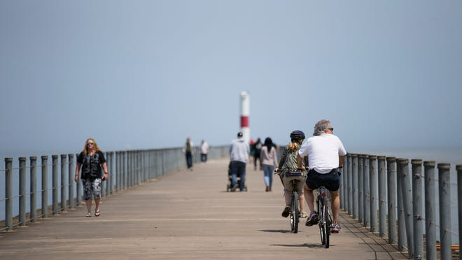 Dan Nigro and Melody Kimmel, who were visiting form New Jersey, bike up the Charlotte Pier at Ontario Beach Park on Sunday May 24, 2015.