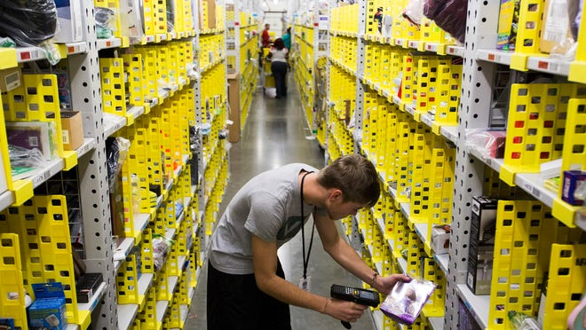 Amazon associate Chris Webster locates an item for shipping at the Amazon Fulfillment Center in Jeffersonville, Ind., during last November's holiday rush.