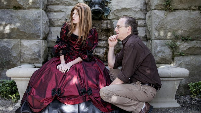 """Author Robert Beatty and daughter, Geneveive, pause under the Biltmore Estate's pergola during the filming of the book trailer for """"Serafina and the Black Cloak."""" Beatty's first novel is set at the Biltmore Estate and geared toward middle school readers. Disney's publishing arm picked up the book and plans to launch in July with 15,000 copies for first printing."""