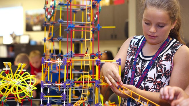 Bella Burke works on a model of an amusement park created during summer robotics camp in the Higley Unified School District. The students designed the park to run off of hydro-electric power.