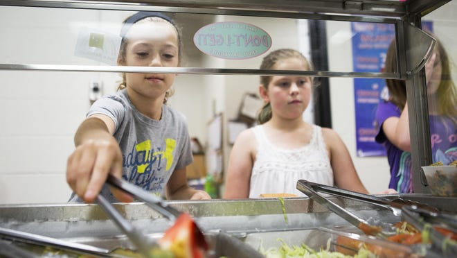 Jordan Chizuk, a fourth-grader at Victor Intermediate School, reaches for vegetables to put on her tray earlier this month. Federal school lunch standards call for serving more fruits and vegetables, but some food services employees say that leads to more waste when kids won't eat them.
