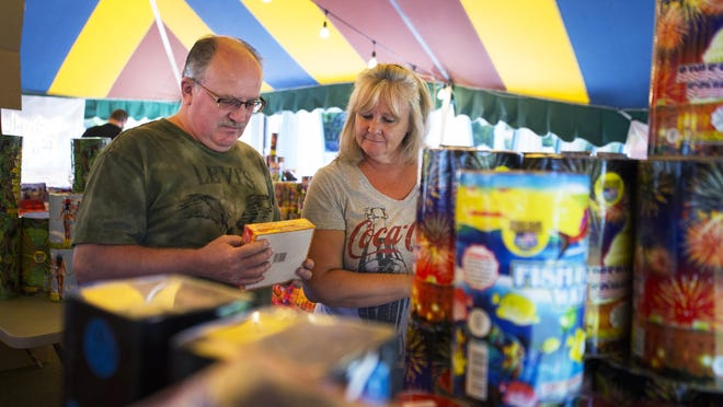 Ken and Pam Hawkins of Ontario pick out fireworks for their Fourth of July celebration in the Barely Legal Fireworks tent in Ontario on Wednesday.