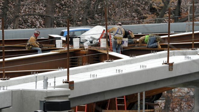 Iron workers are shown attaching plates on structural beams during construction of the Crane Road Bridge in this file photo.