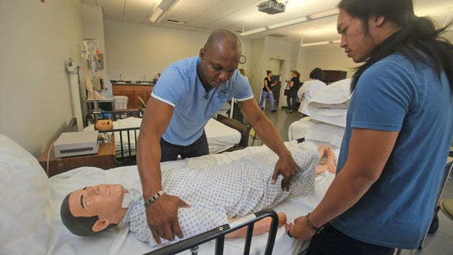 Clivans Lalanne, of Spring Valley, left, and Balvincent Molabola, of Orangeburg, both nursing students at Rockland Community College, practice positioning a patient in the school's Nursing Simulation Lab in September 2014.