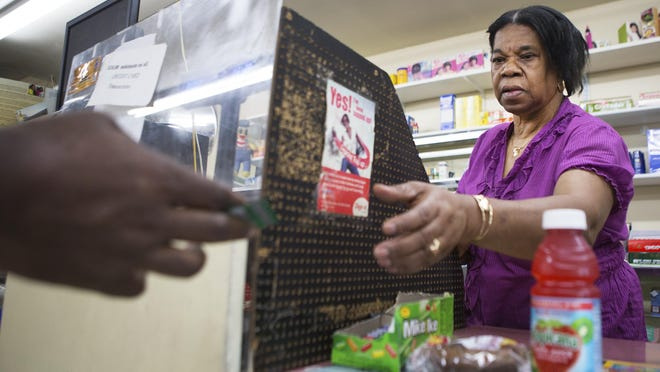 Deloris Hamilton checks out a customer at D&L Groceries on Genesee Street earlier this month.
