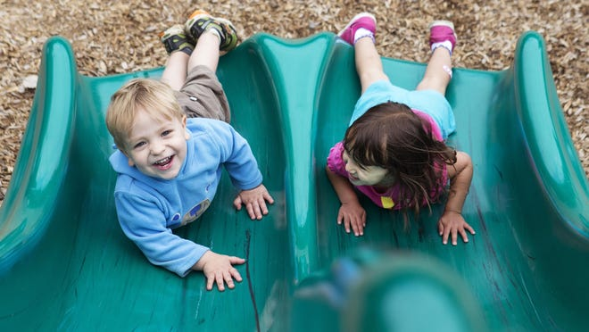 Owen Pouliot, 2, of Penfield and Maya Mohd Sani, 3, of Pittsford slide down a slide together at Penfield's Abraham Lincoln Park.
