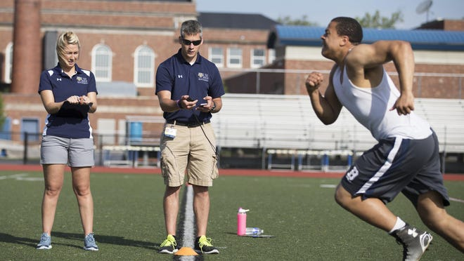 Emily Gunther and Ian Hurlburt with University of Rochester Sports Medicine time Johnell Gamble, a Brighton High School junior, as he completes a pro-agility test during a sports camp in May.