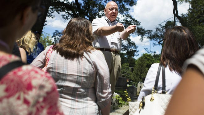 Dennis Carr, a Friends of Mt. Hope volunteer, talks about Otis Cole, the man who arrested Susan B. Anthony, at his grave as he gives a tour in Mt. Hope Cemetery.