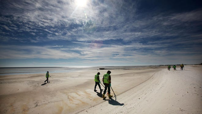 WAVELAND, MS - DECEMBER 06: Workers clean tarballs from the BP oil spill on Waveland beach December 6, 2010 in Waveland, Mississippi. Nearly eight months after the spill, tarballs are still washing up on the beach. BP lawyers said that government estimates of the size of the oil spill are too large in a dispute that will mark how many billions of dollars in fines the oil giant will have to pay. (Photo by Mario Tama/Getty Images)