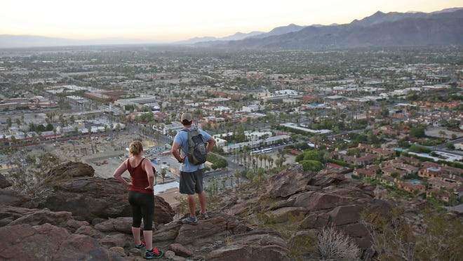 Hikers pause to take in the view overlooking Palm Springs on the Skyline Trail just before sunrise on Tuesday. It's among the most challenging hikes in the nation, experts say.