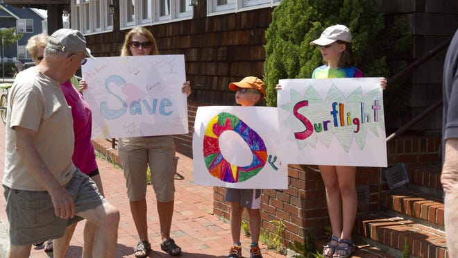 Jen Crawford, a summer resident of Beach Haven, and her children Charlie, 8 and Abby, 10, hold up signs during the auction of the Surflight. It is unclear if the landmark theater will survive or will be demolished to make room for new development.