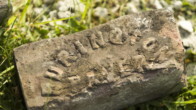 A brick from Purington Brick Co. of East Galesburg, Ill., sits alongside Harrison Street in Davenport, Iowa. Construction has turned up railroad ties that supported trolley cars of the 1920s and the old brick road that existed before concrete was poured over the top.