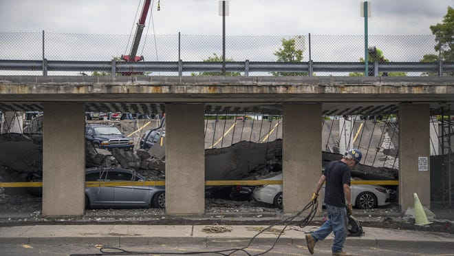 A worker walks past the collapsed parking garage at UHS Wilson Medical Center in Johnson City in this July photo.
