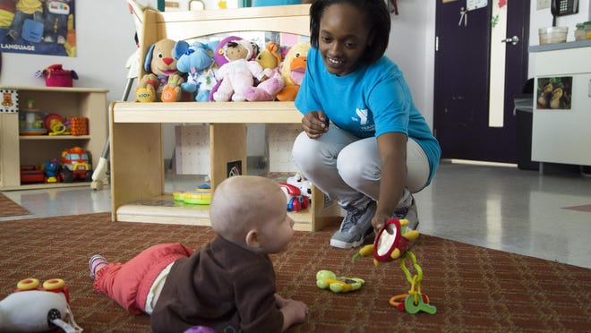 Lakeisha Johnson, an assistant teacher at the Binghamton YMCA, plays with a months-old baby before naptime on Wednesday, September 16, 2015.