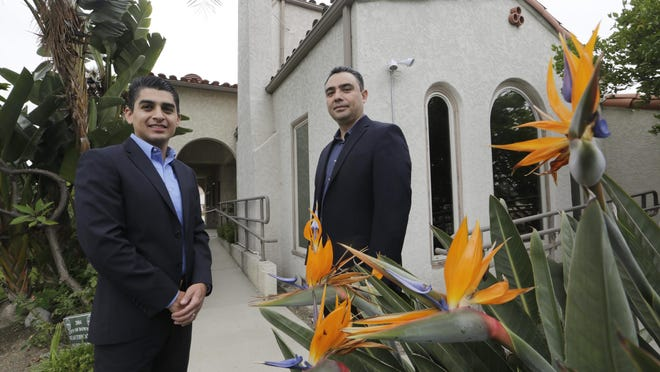 Certified financial planners Gilbert Cerda and Aaron Munoz pose for a photo at their offices in Downey, Calif.