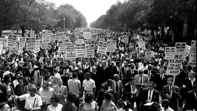 Dr. Martin Luther King Jr., center with arms raised, marches along Constitution Avenue with other civil rights protesters carrying placards as they walked from the Washington Monument to the Lincoln Memorial for the March on Washington, Aug. 28, 1963.