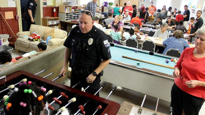 Davenport Police Cpl. Barry Peiffer plays foosball as people gather for a weekly cookout at Lydia House in Davenport.