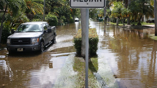 A vehicle navigates flooded streets caused by what many say are rising sea levels because of climate change in September in Ft. Lauderdale, Fla.