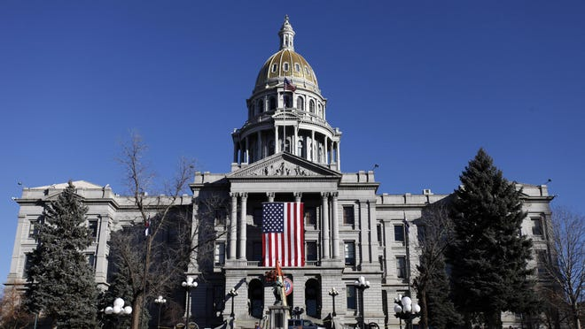 Workers install a large U.S. flag and a Colorado State Seal on the west side of the Capitol in Denver in 2011. The Colorado state government was recently given a D+ in an integrity report by a national nonprofit.