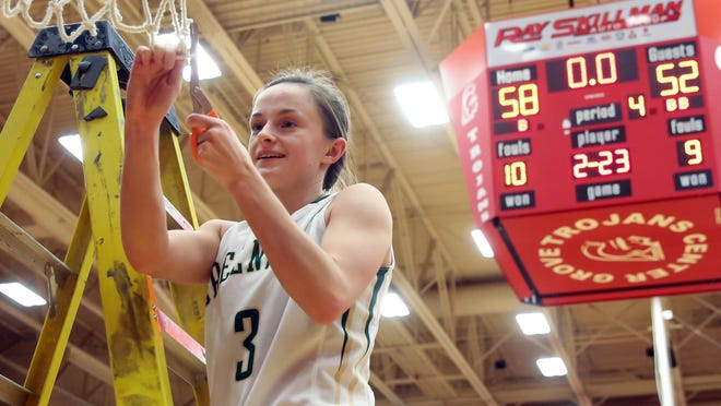 Greenwood's Maddy Renfro cuts down a piece of the net after the team's Johnson County tournament title win Saturday.
