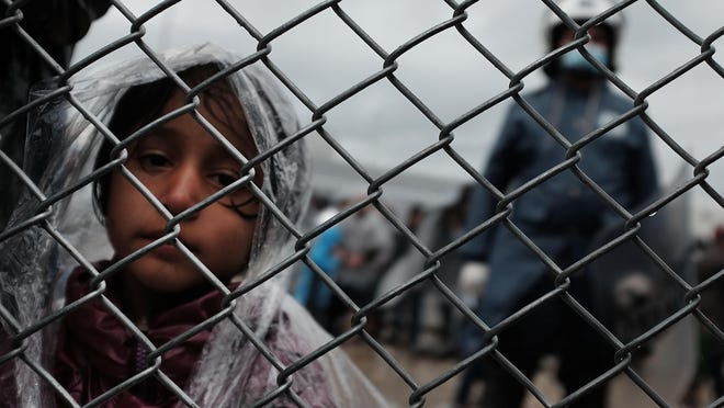 A child waits with her father at a migrant processing center at a camp on the island of Lesbos on Oct. 23 in Mytilene, Greece. Thousands of people have been fleeing conflict in Iraq, Syria, Afghanistan and other countries.