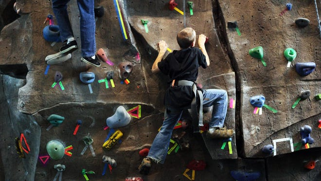 Kids climb the rock wall at the Kroc Center.