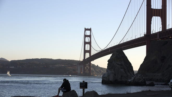 A man sits on a rock overlooking the Golden Gate Bridge at Fort Baker in the Golden Gate National Recreation Area in San Francisco.