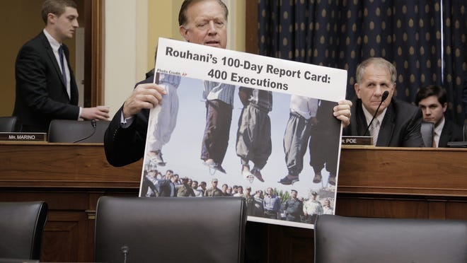 Rep. Randy Weber, R-Texas, carries in a poster accusing Iranian President Hassan Rouhani of hundreds of executions before a House Foreign Relations Committee hearing. (T.J. Kirkpatrick, Getty Images)