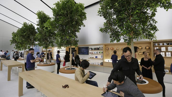 """People try products in the """"Genius Grove"""" during a preview of the new Apple Union Square store on Thursday in San Francisco."""