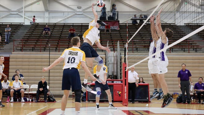 Cathedral's Spencer Smith (9) attempts to spike the ball past two Brownsburg defenders.