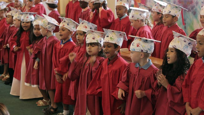 The pre-school graduates perform a song for parents and friends.