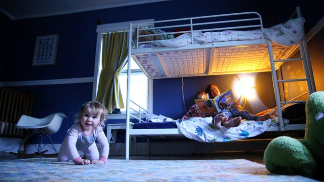 Penelope, 12 months, crawls on the floor as Sarah Coleman reads to her two other children, Phoebe, 5, and Owen, 3. Coleman, like many parents today, lets her children share a bedroom.