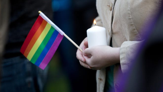 A woman holds a candle and a pride flag during a vigil for the Orlando shooting victims at Memorial Park in Provo, Utah, on June 13. More than 200 people attended the event which featured speakers from local groups.