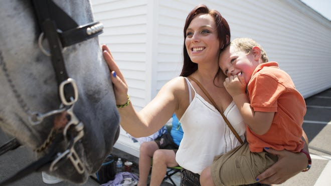 Amanda Eichas of Hilton teaches her son, Aiden, how to pet a horse at Spencerport Canal Days last summer.