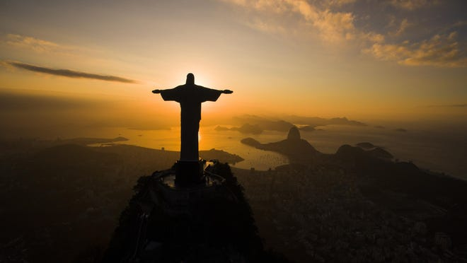 The sun rises behind the Christ the Redeemer statue, above the Guanabara bay in Rio de Janeiro, Brazil, Tuesday, July 19, 2016. With the Olympics set to start on Aug. 5, the games and the city have been overshadowed by security threats, violence, the Zika virus and a national political corruption scandal. (AP Photo/Felipe Dana)