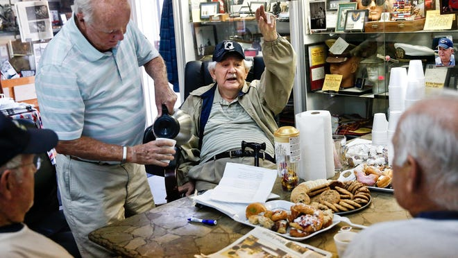Harold Leavitt, center, shares a story with Richie Twiefel, right, Des Johnson, left, and Henry Garretson at Homer Helter's Military and Antiques Mall in North Naples on Jan. 6.