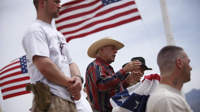 Rancher Cliven Bundy, flanked by armed supporters, speaks at a protest camp April 18, 2014, near Bunkerville, Nev.