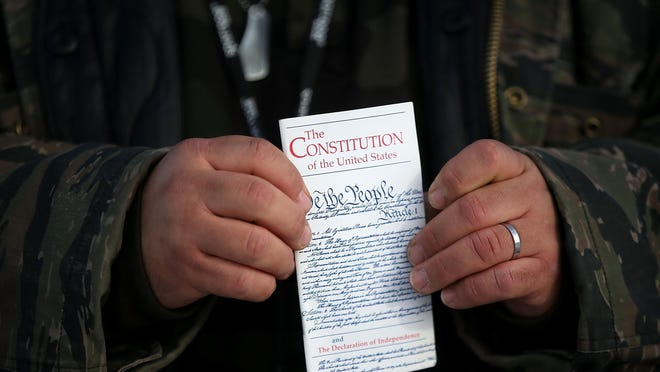 BURNS, OR - JANUARY 06: A member of an anti-government militia holds a copy of the U.S. Constitution at the Malheur National Wildlife Refuge Headquarters on January 6, 2016 near Burns, Oregon. An armed anti-government militia group continues to occupy the Malheur National Wildlife Headquarters as they protest the jailing of two ranchers for arson. (Photo by Justin Sullivan/Getty Images)