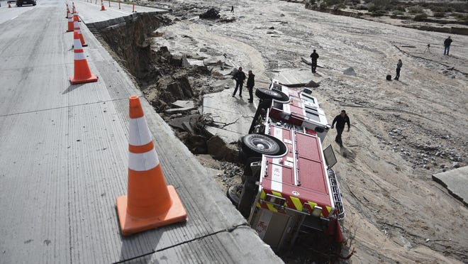 Officials look over the scene where a San Bernardino County Fire Department fire engine fell Friday from southbound Interstate 15 where part of the freeway collapsed due to heavy rain in the Cajon Pass.