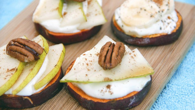 Sweet potato toasts are made with slices of sweet potato, covered with pear and yogurt and topped with a pecan.