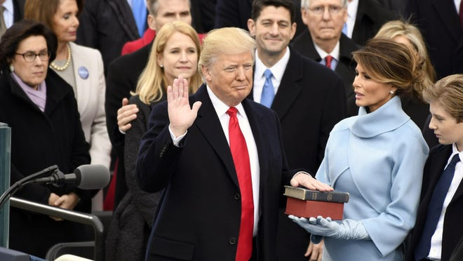 Jan 20, 2017; Washington, DC; Donald Trump takes the oath of office during the 2017 Presidential Inauguration at the U.S. Capitol.