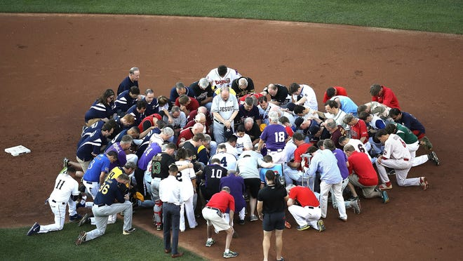 Members of the Republican and Democratic congressional baseball teams gather for a bipartisan prayer before the start of the Congressional Baseball Game at Nationals Park on Thursday in Washington, D.C.