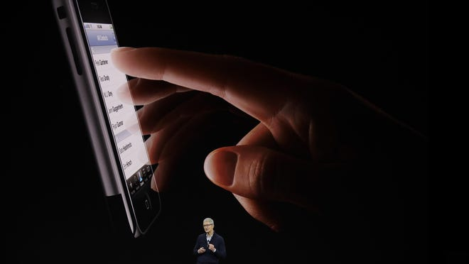 Apple CEO Tim Cook, shows the new iPhone 8 at the Steve Jobs Theater on the new Apple campus on Tuesday, Sept. 12, 2017, in Cupertino, Calif. (AP Photo/Marcio Jose Sanchez)