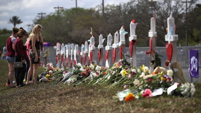 Visitors mourn at a makeshift memorial in front of Marjory Stoneman Douglas High School on Feb. 19, 2018, in Parkland, Fla. Credit: Joe Raedle, Getty Images