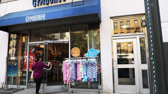 People walk by the children's clothing retailer Gymboree, which has filed for bankruptcy protection on June 13, 2017. Credit: Spencer Platt, Getty Images.