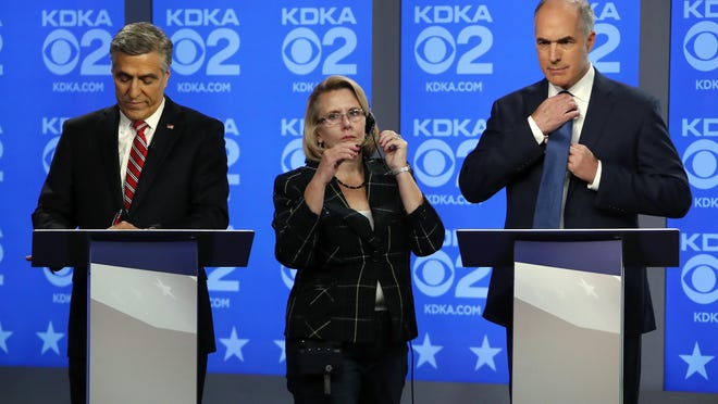 U.S. Sen.Bob Casey, D-PA, right, and Republican challenger U.S. Rep. Lou Barletta, left, are prepped by floor manager Patty Cobb before their second debate, Friday Oct. 26, 2018, in the studio of KDKA-TV in Pittsburgh. Casey, 58, of Scranton, is seeking a third six-year term. Barletta, 62, of Hazleton, is in his fourth term in Congress. (AP Photo/Gene J. Puskar)