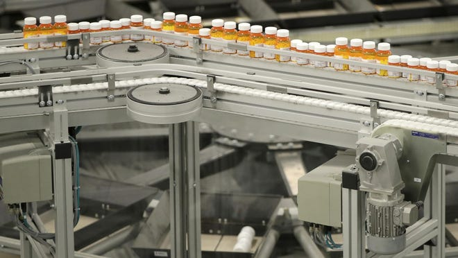 FILE - In this July 10, 2018 file photo, bottles of prescription medicines ride on a conveyor belt at a pharmacy warehouse in Florence, N.J. According to a report released on Tuesday, Jan. 8, 2018, annual spending by the U.S. health industry on ads and promotions has reached $30 billion. That includes advertisements for prescription drugs that were shown 5 million times on TV and elsewhere in 2016. That's a huge increase in 20 years and just part of broad health industry efforts to promote drugs, devices, lab tests and even new hospitals. (AP Photo/Julio Cortez, File)