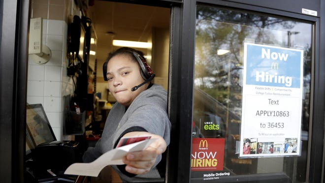 A cashier returns a credit card and a receipt at a McDonald's window, where signage for job openings are displayed in Atlantic Highlands, N.J. U.S. employers posted the most open jobs in December in the nearly two decades that records have been kept, evidence that the job market is strong despite several challenges facing the economy.
