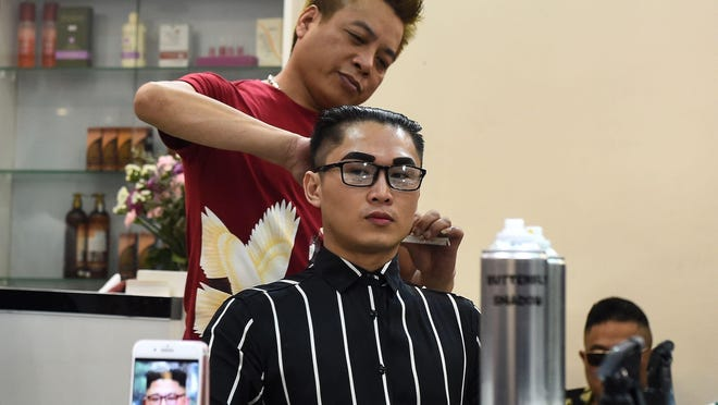 Vietnamese man, Nguyen Huu Thien gets a North Korean leader Kim Jong Un style haircut at a saloon in Hanoi on February 20, 2019.